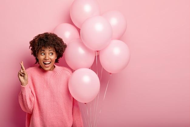 Mulher feliz e cacheada em um macacão grande, com os dedos cruzados para dar sorte, segurando balões de hélio