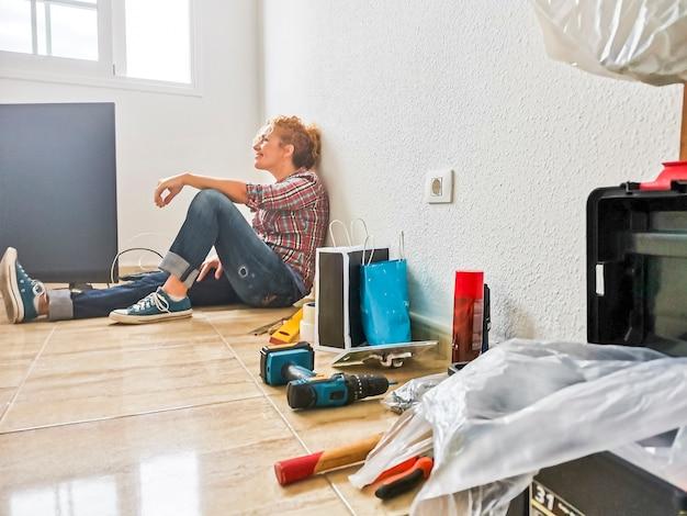 Mulher feliz e cansada descansando no chão depois de trabalhar em casa durante uma hipoteca