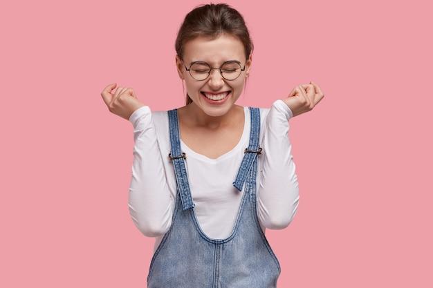 Mulher feliz e contente ri de uma anedota engraçada, abre os punhos, tem um sorriso cheio de dentes, usa óculos redondos e macacão jeans, modelos sobre fundo rosa