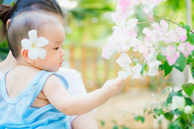 Mulher feliz e criança no jardim primavera florescendo.