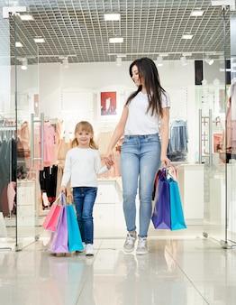 Mulher feliz e criança segurando sacolas de compras na loja.