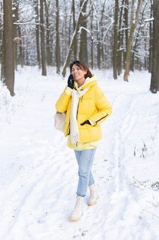 Mulher feliz e de ótimo humor caminha pela floresta de neve de inverno e conversa animadamente ao telefone, aproveitando o tempo ao ar livre no parque