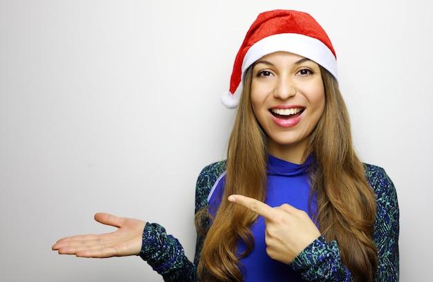 Mulher feliz e desportiva com chapéu de papai noel mostrando e apontando o dedo