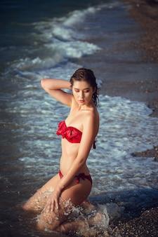 Mulher feliz e despreocupada, apreciando o belo pôr do sol na praia.