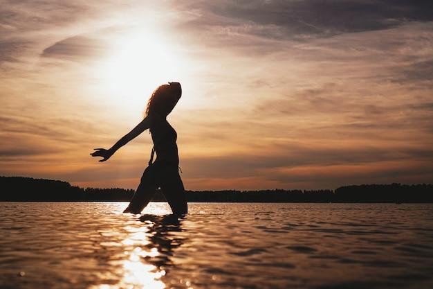 Mulher feliz e despreocupada curtindo o belo pôr do sol na praia