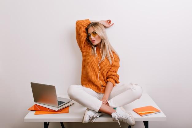 Mulher feliz e elegante em calças brancas da moda, brincando no escritório, sentada com as pernas cruzadas à mesa perto do computador