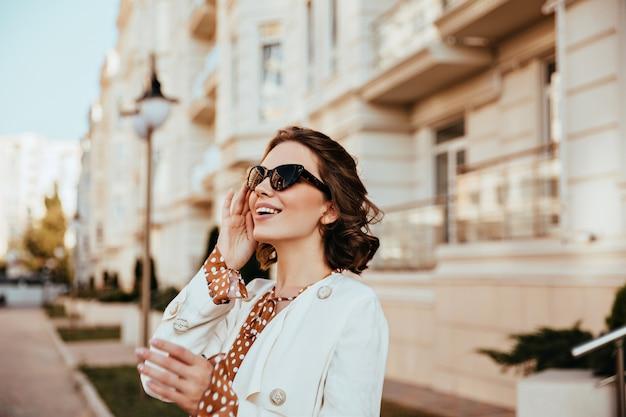 Mulher feliz e elegante posando perto de grande edifício antigo. menina caucasiana refinada em pé na cidade de borrão bakground no dia de outono.