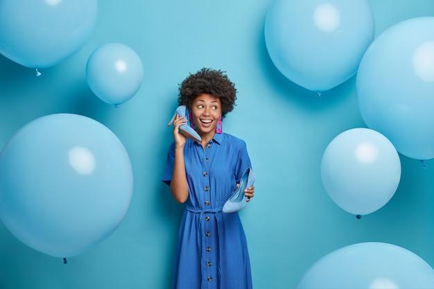 Mulher feliz e elegante se prepara para a festa de aniversário, segura sapatos de salto alto perto da orelha enquanto o telefone, vestida com roupas festivas, se diverte, poses