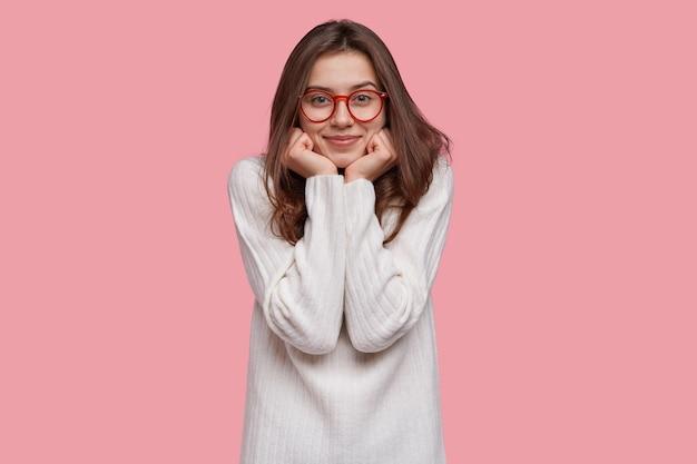 Mulher feliz e encantada segura o queixo com as duas mãos, usa óculos de aro vermelho e suéter branco comprido, tem um sorriso gentil no rosto