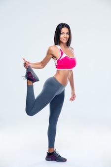 Mulher feliz e esportiva esticando a perna