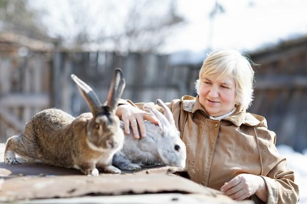 Mulher feliz e fazenda de coelhos. gado doméstico