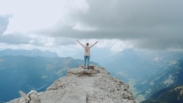 Mulher feliz e livre com as mãos estendidas no topo da rocha