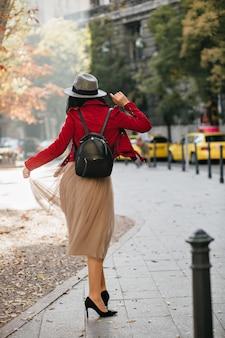 Mulher feliz e magra com sapatos de salto alto pretos dançando no parque em dia de outono