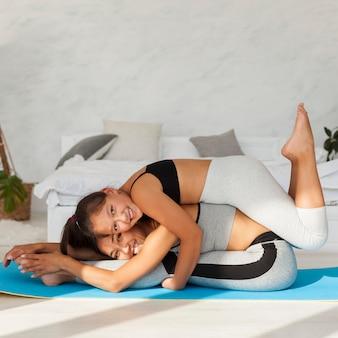 Mulher feliz e menina com tapete de ioga