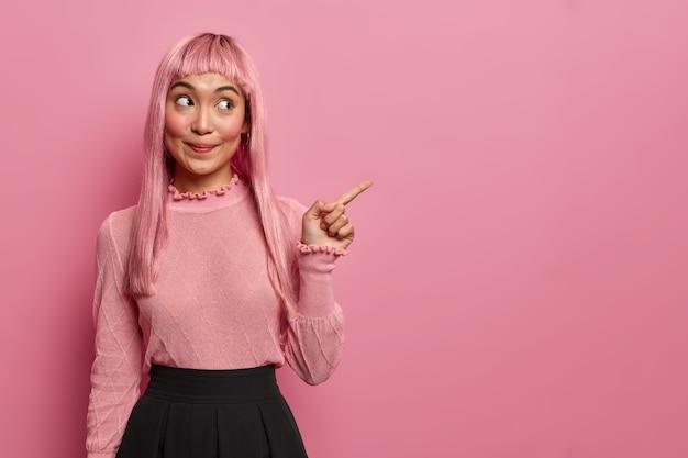 Mulher feliz e misteriosa do leste tem cabelo comprido, aponta o dedo para o espaço da cópia, mostra o lugar para o seu anúncio, promove o banner da empresa ou produto
