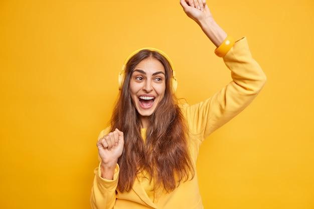 Mulher feliz e otimista de cabelos compridos faz dança triunfante levanta os braços aprecia a música favorita ouve canções através de fones de ouvido brinca isolado sobre a parede amarela. conceito de estilo de vida e passatempo