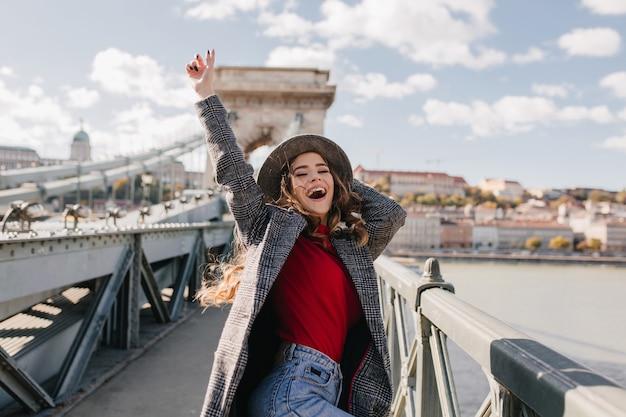 Mulher feliz e pálida em um casaco expressando emoções verdadeiras enquanto posa na ponte em um dia quente