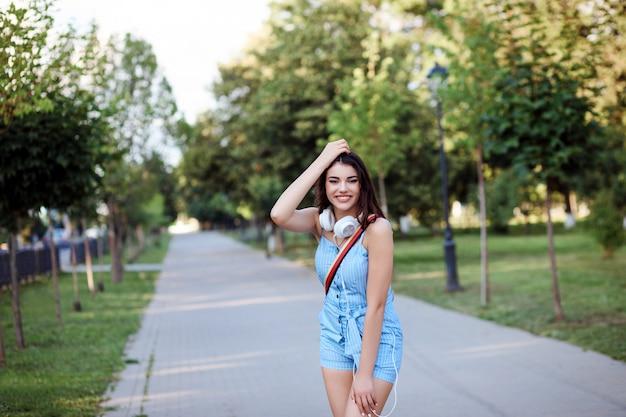 Mulher feliz é passar o tempo ao ar livre no parque no verão.