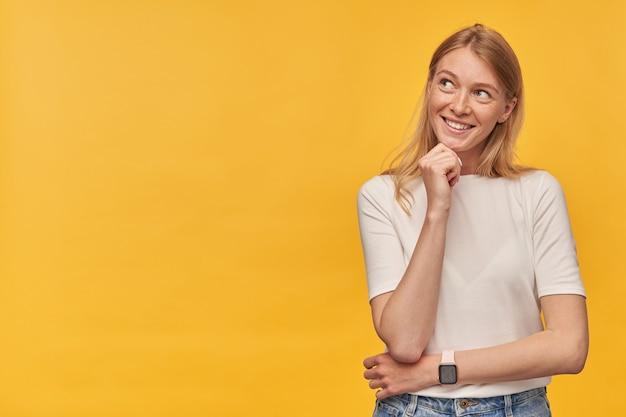 Mulher feliz e pensativa com sardas na camiseta branca, pensando e olhando para o lado, na sombra amarela