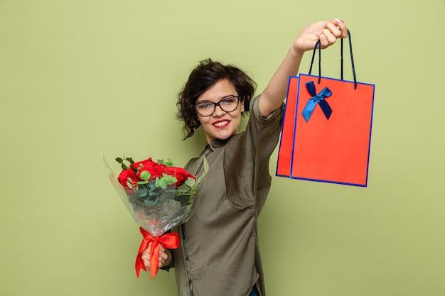 Mulher feliz e positiva com cabelo curto, segurando um buquê de flores e um saco de papel com presentes sorrindo alegremente, comemorando o dia internacional da mulher, 8 de março.