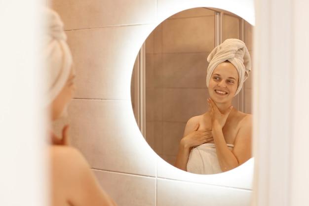 Mulher feliz e positiva com pele fresca, olhando no reflexo no espelho depois do banho, enrolado em uma toalha branca em pé, posando no banheiro ao fazer procedimentos matinais.