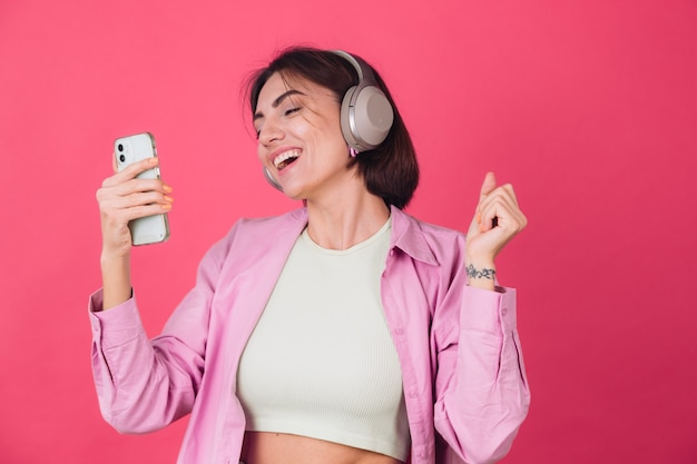 Mulher feliz e positiva em fones de ouvido na parede rosa vermelha
