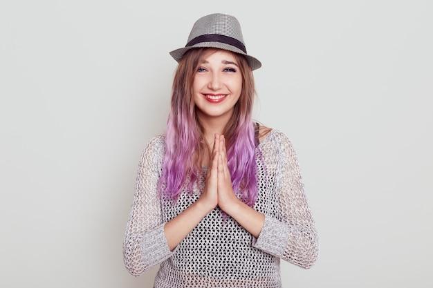 Mulher feliz e positiva junta as palmas das mãos, pedindo a alguém, orando, expressando gratidão, tem um sorriso dentuço, isolado sobre uma parede branca.