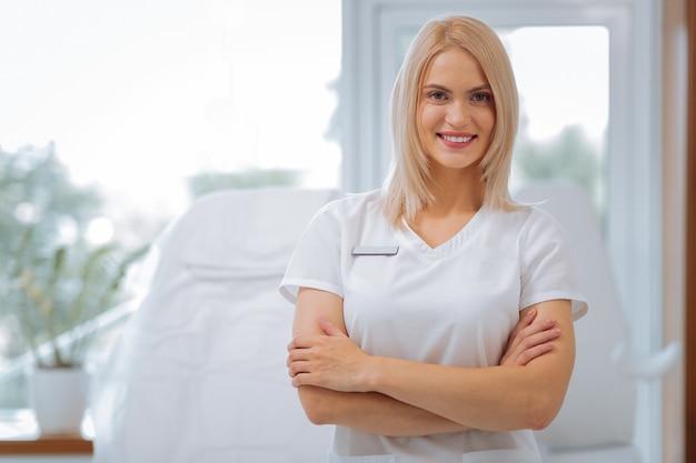 Mulher feliz e positiva sorrindo para você enquanto trabalhava como cosmetologista na clínica