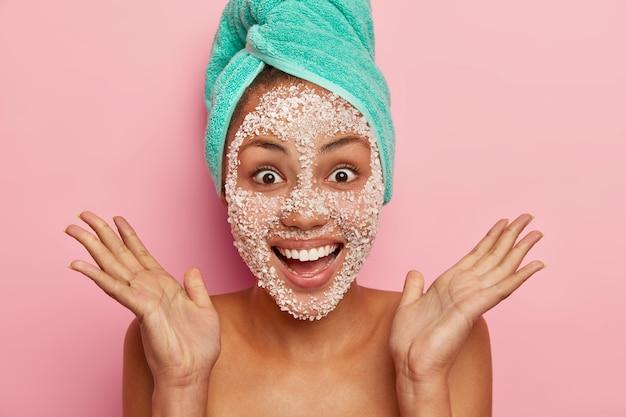 Mulher feliz e radiante espalha as palmas das mãos perto do rosto, tem um sorriso dentuço, uma máscara de sal marinho branco, usa uma toalha turquesa embrulhada, fica sem camisa sobre uma parede rosada