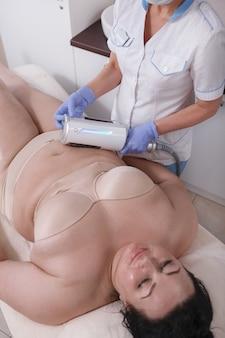Mulher feliz e relaxada com excesso de peso desfrutando de massagem corporal com endosferas
