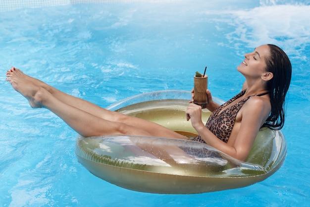 Mulher feliz e relaxante nadando em boia na piscina, desfrutando de um coquetel tropical