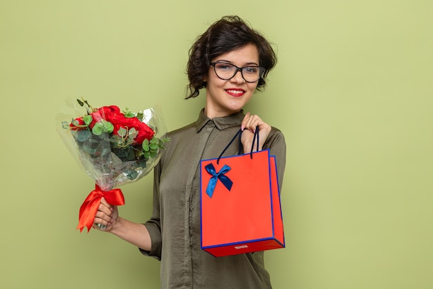 Mulher feliz e satisfeita com cabelo curto segurando um buquê de flores e um saco de papel com presentes sorrindo alegremente, comemorando o dia internacional da mulher, 8 de março