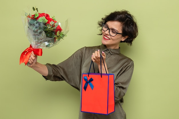 Mulher feliz e satisfeita com cabelo curto segurando um buquê de flores e um saco de papel com presentes sorrindo alegremente