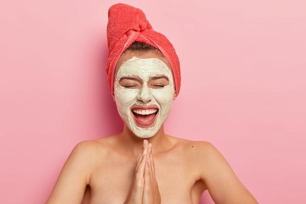 Mulher feliz e satisfeita mantém as palmas das mãos em gesto de oração, sorri amplamente, usa máscara facial para rejuvenescimento, se diverte em casa, posa nua com os ombros nus, isolada na parede rosa