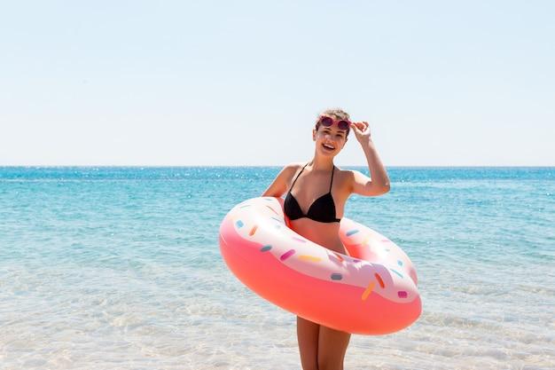 Mulher feliz e saudável em biquíni preto na costa do oceano segurando um anel inflável rosa. férias de verão e o conceito de férias.