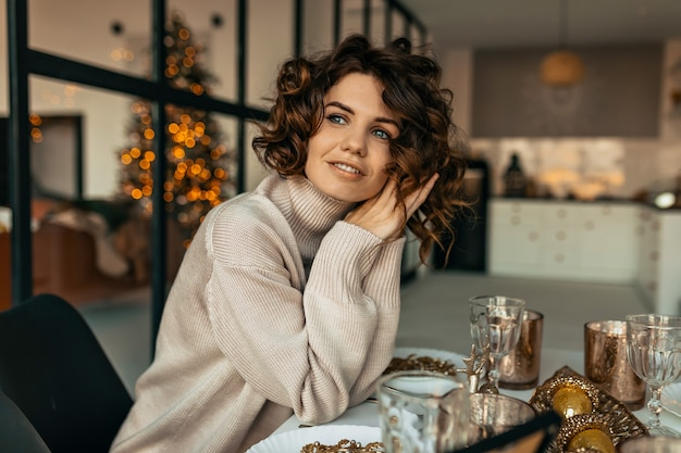 Mulher feliz e sonhadora com penteado encaracolado vestida de suéter bege de malha sentada à mesa de natal sobre a árvore de natal