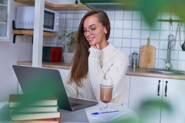 Mulher feliz e sorridente aconchegante vestindo um suéter branco quente e óculos redondos com uma xícara de chocolate quente trabalhando remotamente on-line no laptop em uma cozinha aconchegante