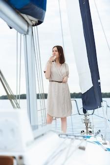 Mulher feliz e sorridente bebendo coquetéis de vodka na festa do barco ao ar livre, alegre e linda