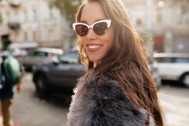 Mulher feliz e sorridente com cabelo escuro comprido e ondulado, óculos elegantes e casaco de pele, olhando para a câmera na luz do sol na cidade