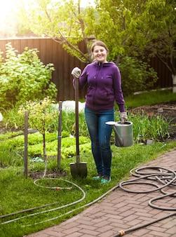 Mulher feliz e sorridente com ferramentas de jardim em dia de sol