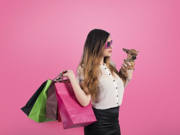 Mulher feliz e sorridente com sacolas de compras na mão em fundo rosa