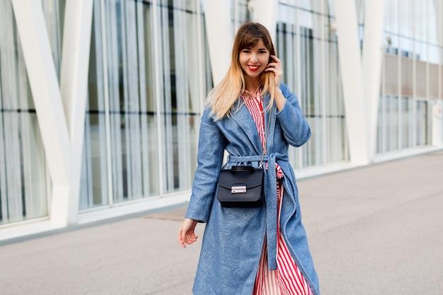 Mulher feliz e sorridente com um elegante casaco azul e vestido listrado vermelho, caminhando no moderno centro de negócios