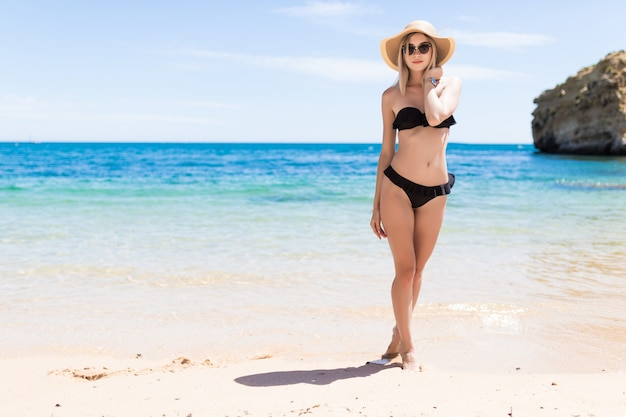 Mulher feliz e sorridente de biquíni e chapéu de sol na praia do mar
