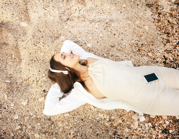 Mulher feliz e sorridente deitada na areia do mar e ouvindo música