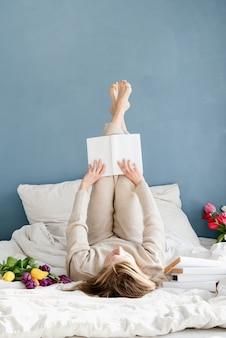 Mulher feliz e sorridente deitada na cama de pijama, com prazer, curtindo flores e lendo um livro