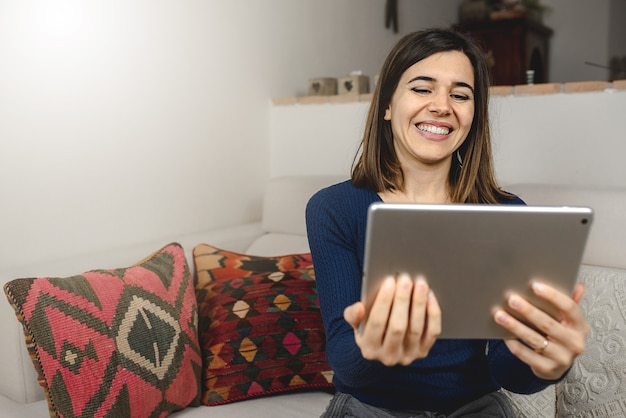 Mulher feliz e sorridente em casa usando dispositivo eletrônico para fazer uma videochamada com amigos ou familiares