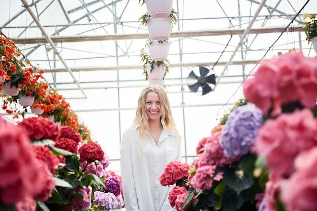 Mulher feliz e sorridente em pé perto de lindas flores cor de rosa. estufa industrial com hortênsias coloridas. jovem loira em uma estufa. flores em vasos ao redor.