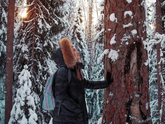 Mulher feliz e sorridente em roupas quentes com um capuz na cabeça toca a casca da árvore. unidade com a natureza. bela floresta de pinheiros sob a neve, inverno gelado.
