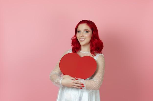 Mulher feliz e sorridente em um vestido branco e cabelo ruivo segurando um grande coração de papel vermelho