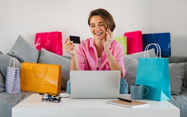 Mulher feliz e sorridente em uma camisa rosa no sofá em casa entre sacolas coloridas segurando um cartão de crédito e pagando online no laptop